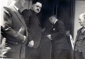 The important moment! D D Davies Maesllan (chairman) faces camera.  E L Jones (secretary) looks on from the right, while Mr D Idris Davies Dinas Quarries formally opens the Hall door.  The figure on the left may be John Simon the Hall architect.